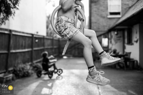 Un garçon joue sur une balançoire faite maison tandis que son frère monte un tricycle sur cette photo enregistrée par un photographe de famille de style documentaire primé à Surrey, en Angleterre.