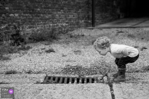 Un petit garçon se penche pour jeter un coup d'œil dans un collecteur d'eaux pluviales sur cette photo prise par un photojournaliste de famille de Bruxelles, en Belgique.