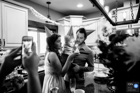 Un père tient un bébé alors que sa mère lui tient un gâteau d'anniversaire sur cette photo d'un photographe de famille primé à Seattle, WA.