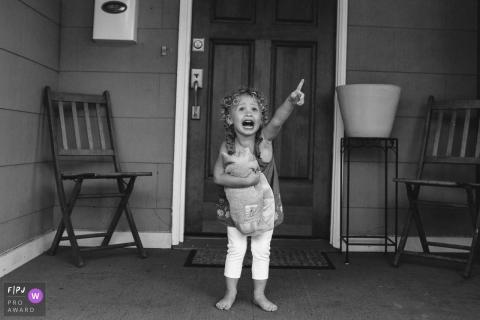 Une petite fille se tient sur un porche qui pointe vers le ciel sur cette photo créée par un photojournaliste de la famille de Seattle, WA.