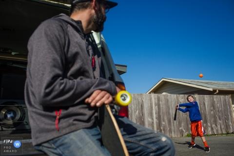 Un père observe que son fils est sur le point de frapper une balle de baseball dans cette image de famille de style documentaire enregistrée par un photographe de San Francisco, Californie.