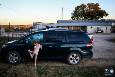Une petite fille vêtue d'un ballet tient sa jambe derrière elle alors qu'elle s'accroche à la fourgonnette familiale dans le cadre de ce concours photo récompensé par la Family Photojournalist Association, créé par un photographe de famille de San Francisco, Californie.