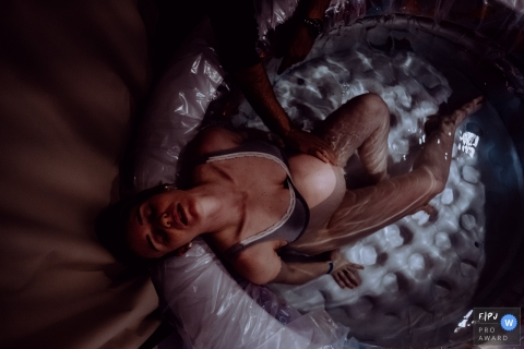 A woman tries to relax in her birthing tub just before her at home water birth in this image created by a documentary Santa Catarina, Brazil birth photographer.