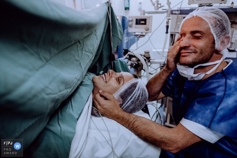 A husband wipes away a tear and sits with his wife during her C-section in the hospital in this photo composed by a Santa Catarina, Brazil birth photographer.