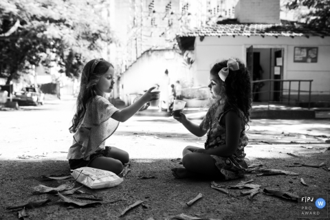 Two girls enjoy cool drinks together outside in this Family Photojournalist Association contest awarded photo created by a Rio de Janeiro, Brazil family photographer.
