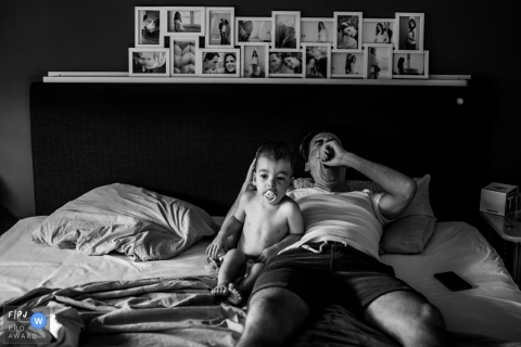 A baby boy sits with his father who lays in bed yawning next to him in this photograph by an Eindhoven, Noord Barbant documentary family photographer.