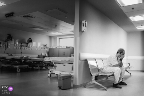 A father waits anxiously in the hospital hallway while his wife gives birth in this black and white image captured by a documentary-style Rio de Janeiro, Brazil birth photographer.