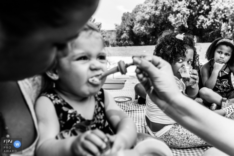 Two girls watch as a little girl cringes while her mother feeds her lunch in this image created by a Rio de Janeiro, Brazil family photographer.