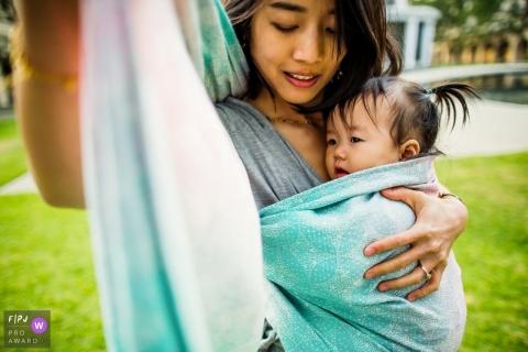 Une mère enveloppe sa petite fille dans un papier photo sur cette photo enregistrée par un photographe de famille de style documentaire primé à San Francisco, Californie.