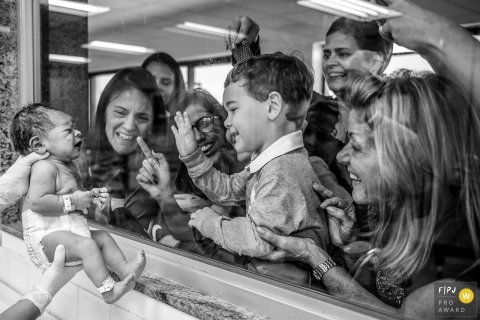 A family waves through the hospital window at their newest family member in this black and white photo by a Rio de Janeiro, Brazil birth photographer.