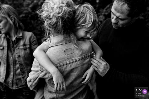 Un père et une mère tentent de réconforter leur enfant en pleurs sur cette image capturée par un photojournaliste de la famille flamande.