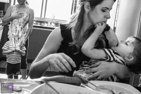 Un petit garçon cache son visage sous une chemise de femme tandis que sa mère tient son petit frère sur cette photo réalisée par un photojournaliste de la famille Minas Gerais.