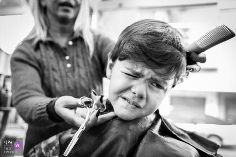 Un petit garçon grimace en se faisant couper les cheveux dans cette image de famille de style documentaire enregistrée par un photographe de Minas Gerais.