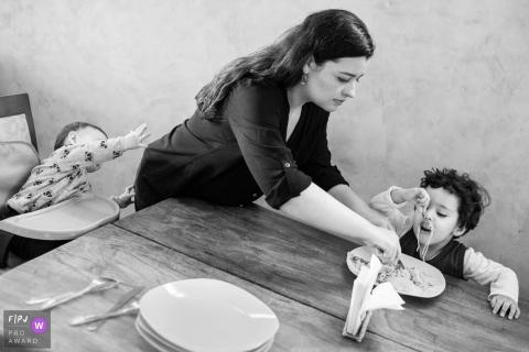 Un petit garçon cherche sa mère pendant qu'elle aide son frère, qui joue avec ses spaghettis dans le cadre de ce concours récompensant une photo de la famille des photojournalistes de famille créé par un photographe de la famille Minas Gerais.