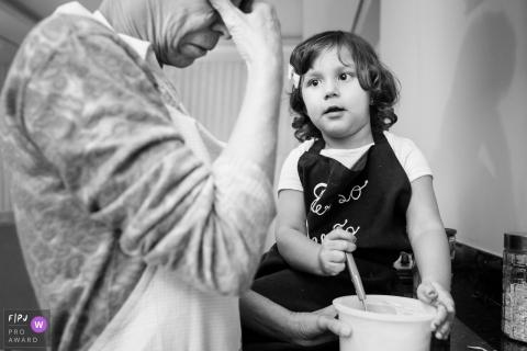 Un homme cache son visage pendant qu'une petite fille essaie de l'aider dans la cuisine sur cette image primée du FPJA par un photographe de la famille Minas Gerais.