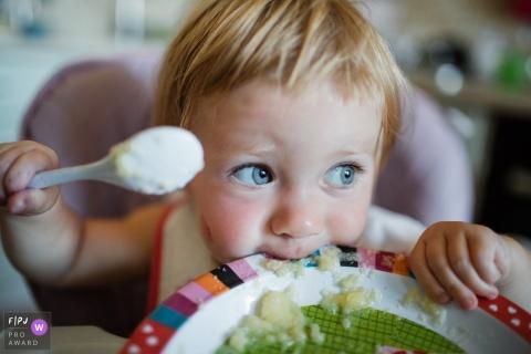 Un petit garçon mange sa nourriture directement de l'assiette dans cette photo de famille de style documentaire prise par un photographe de Saint-Pétersbourg, en Russie.