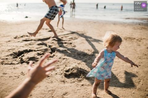 Une petite fille se promène le long d'une plage alors que d'autres jouent en arrière-plan dans cette photo de famille réalisée par un photographe de Saint-Pétersbourg, en Russie.
