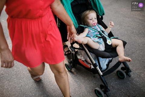 A mother holds her daughter's foot while she sits in her stroller in this photograph by a Saint Petersburg, Russia documentary family photographer.