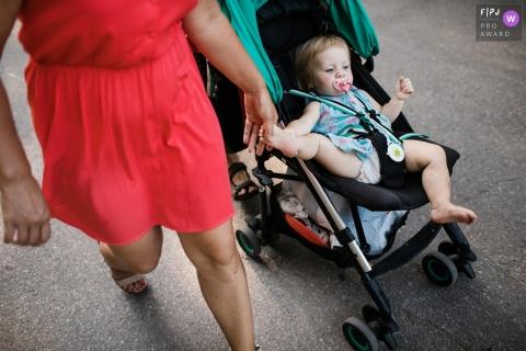 Une mère tient le pied de sa fille pendant qu'elle est assise dans sa poussette sur cette photo réalisée par un photographe de famille documentaire de Saint-Pétersbourg, en Russie.