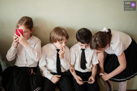 Quatre jeunes enfants jouent ensemble au téléphone dans cette photo de famille décernée par un photographe de famille documentaire de Saint-Pétersbourg, en Russie.