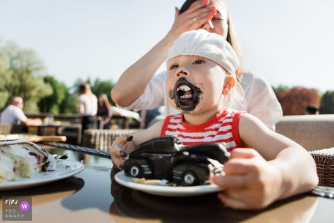 A mother covers her face with her hand while her little boy's face is covered in black frosting from taking a bite out of his car-shaped cake in this award-winning photo by a Saint Petersburg, Russia family photographer.