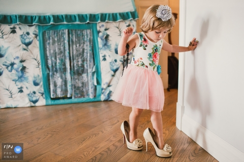 A little girl wearing a dress tries to walk in her mother's high heels in this image created by a Saint Petersburg, Russia family photographer.