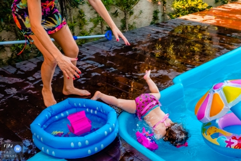 A mother reaches for her little girl who has fallen head-first into a kiddie pool in this picture captured by a Rio Grande do Sul, Brazil family photojournalist.