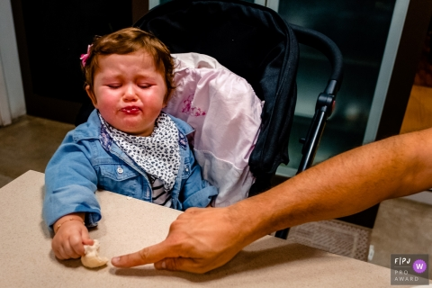 A little girl starts to get upset when her father reaches to touch her food in this photo by a Rio Grande do Sul, Brazil award-winning family photographer.