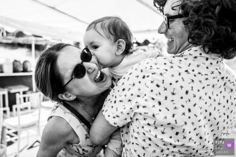 Une mère et un père rient pendant que leur bébé embrasse la mère sur sa joue sur cette photo réalisée par un photojournaliste de famille à Bucarest, en Roumanie.