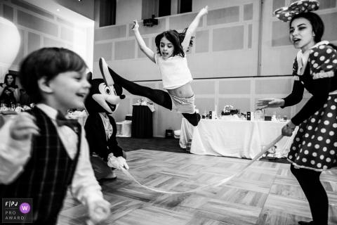 Une fille saute par-dessus une corde tenue par deux personnes habillées en Mickey et Minnie Mouse dans le cadre du concours de l'association des photojournalistes de famille primé avec une photo créée par un photographe de famille de Bucarest, en Roumanie.