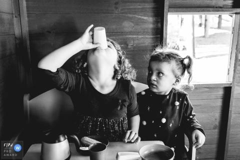 Une fille regarde sa sœur terminer son verre dans cette photo de famille réalisée par un photographe de Curitiba, Parana.