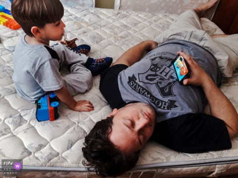 A father and son lay on a bed together watching a video on a smart phone in this photograph by a Curitiba, Parana documentary family photographer.