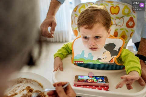 A little boy tries to reach for his food in his high chair in this Family Photojournalist Association awarded photo by a Rio de Janeiro, Brazil documentary family photographer.
