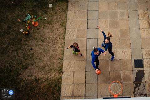 Une mère, un père et son fils jouent au basketball ensemble dans cette photo récompensée par une photo par un photographe de famille documentaire de Rio Grande do Sul, Brésil.
