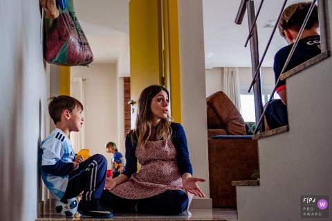Une mère assise sur le sol discutant avec ses deux fils dans cette image primée du FPJA, capturée par un photographe de famille du Rio Grande do Sul, au Brésil.