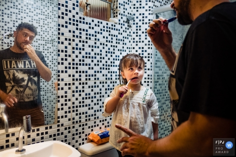 A little girl looks to her father for direction as the two of them brush their teeth together in this award-winning photo by a Rio Grande do Sul, Brazil family photographer.