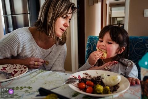 Une mère fait une grimace et place sa main sous le menton de sa fille alors qu'elle tente de se fourrer une grosse bouchée de nourriture dans sa bouche avec cette image créée par un photographe de famille de Rio Grande do Sul, Brésil.