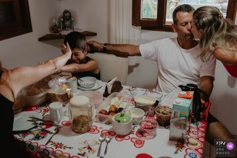 Un mari embrasse sa femme en tapotant la tête de son fils et celui-ci tente de repousser le bras de quelqu'un d'autre sur cette photo prise par un photojournaliste de la famille Santa Catarina, à Florianopolis.