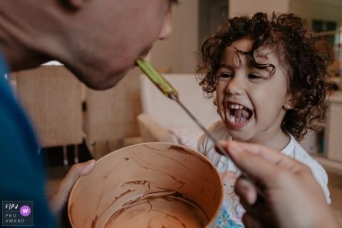 Une petite fille rit tandis que son père lèche une spatule recouverte de pâte sur cette photo réalisée par un photojournaliste de la famille Santa Catarina, Florianopolis.