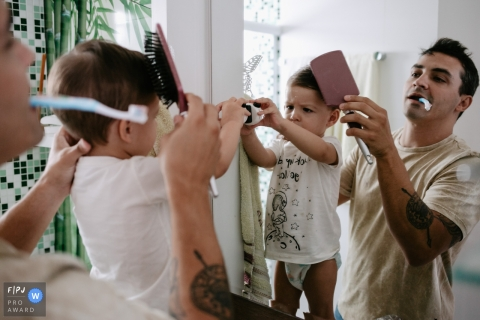 A father holds a toothbrush in his mouth while he brushes his son's hair in this FPJA award-winning picture by a Florianopolis, Santa Catarina family photographer.