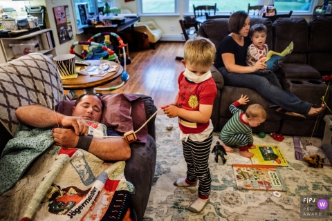 Three children play while their mom reads one of them a book and their father tries to sleep in this documentary-style family photo captured by a Philadelphia, PA photographer.