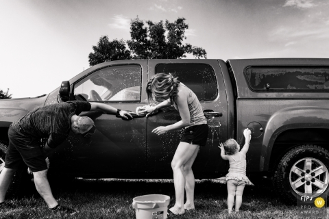 A baby girl tries to help her parents wash their truck in this Family Photojournalist Association awarded photo by a Missoula, MT documentary family photographer.