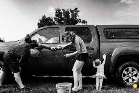 Une petite fille tente d'aider ses parents à laver leur camion dans cette photo récompensée par la photo de famille par un photographe de famille documentaire de Missoula, MT.