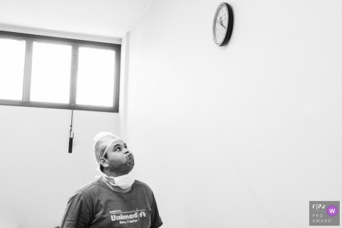 A soon-to-be father looks anxiously up at the clock on the hospital wall as he waits while his wife gives birth in this black and white photo by a Rio de Janeiro, Brazil birth photographer.