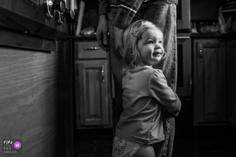 A little girl holds onto her father's leg in this FPJA award-winning image captured by a Connecticut family photographer.