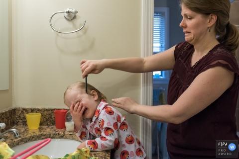 Une petite fille se couvre le visage et pleure tandis que sa mère se peigne les cheveux sur cette photo primée d'un photographe de la famille du Connecticut.