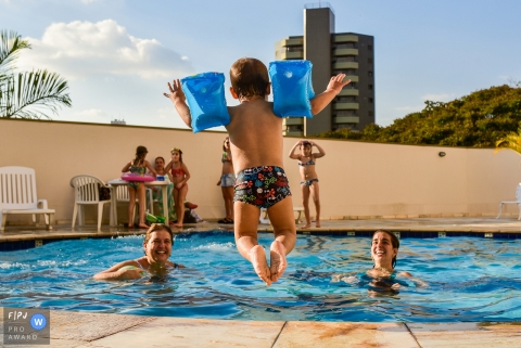 A little boy wearing floaties jumps into a pool where his family waits for him in this image created by a Campinas, Sao Paulo family photographer.