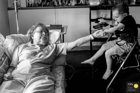 A boy and his grandmother hold hands as she lays on the couch in this picture captured by a Connecticut family photojournalist.