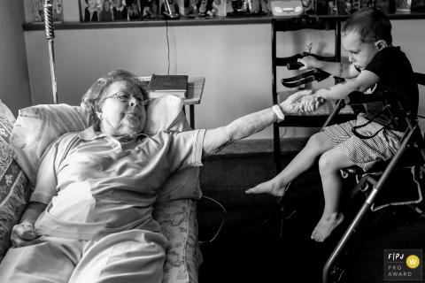 Un garçon et sa grand-mère se tiennent par la main alors qu'elle s'allonge sur le canapé dans cette photo prise par un photojournaliste de la famille du Connecticut.