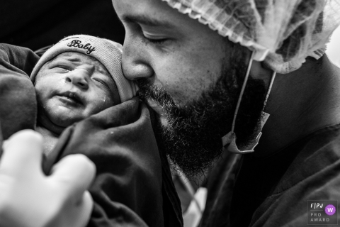 A father holds and kisses his newborn infant in the hospital for the first time in this black and white photo by a Campinas, Sao Paulo birth photographer.